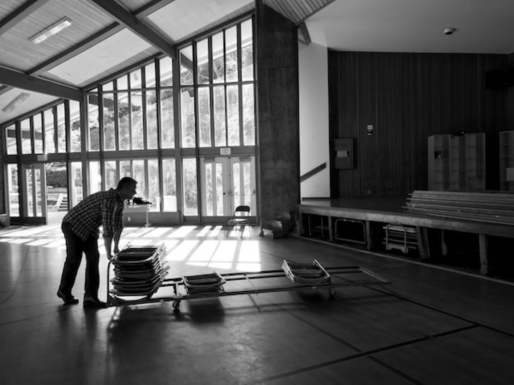 Man pushing cart of folding chairs in front of large window. Black and white photo take at Strawberry Rec Center in Mill Valley