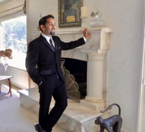 Zubin standing in front of mantel in suit